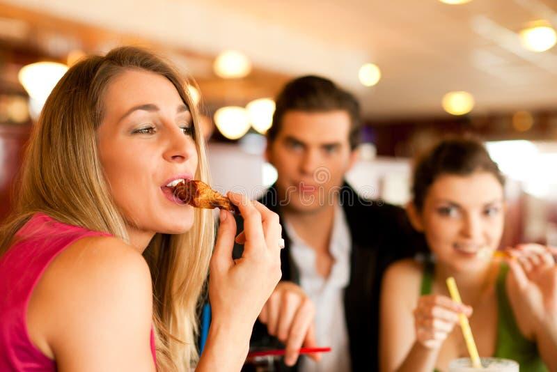 Vrienden die in Restaurant snel voedsel eten stock foto's