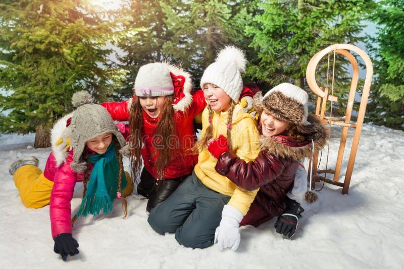 Vrienden die samen bij de winterspelen spelen op sneeuw stock afbeeldingen