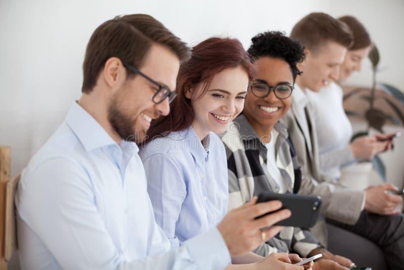 Vrienden die samen binnen grappige video op telefoonzitting kijken stock fotografie