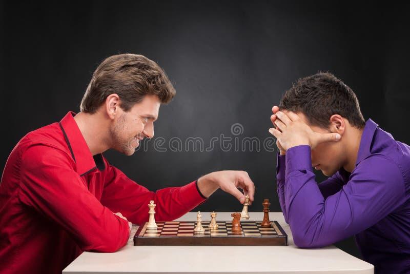 Vrienden die schaak op zwarte achtergrond spelen stock foto