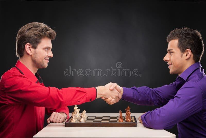 Vrienden die schaak op zwarte achtergrond spelen stock foto's