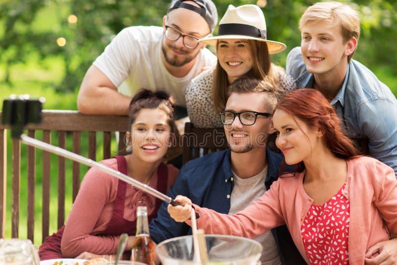 Vrienden die selfie bij partij in de zomertuin nemen stock foto's
