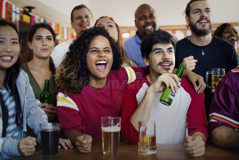 Vrienden die sport samen toejuichen bij bar stock foto