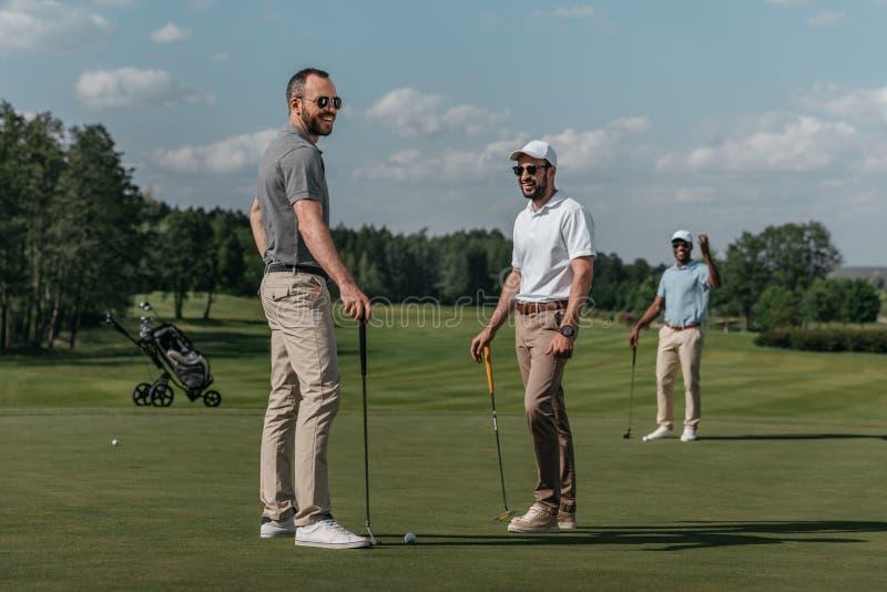 Vrienden die terwijl samen het spelen van golf op groen bij dag spreken stock fotografie