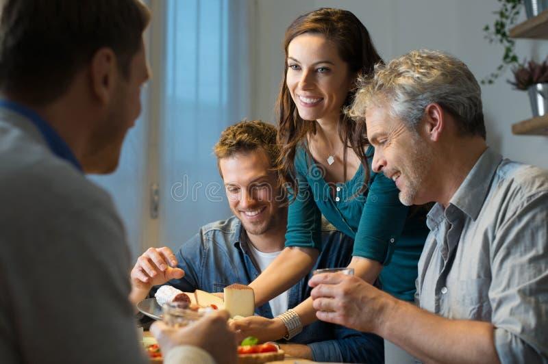 Vrienden die thuis eten stock fotografie