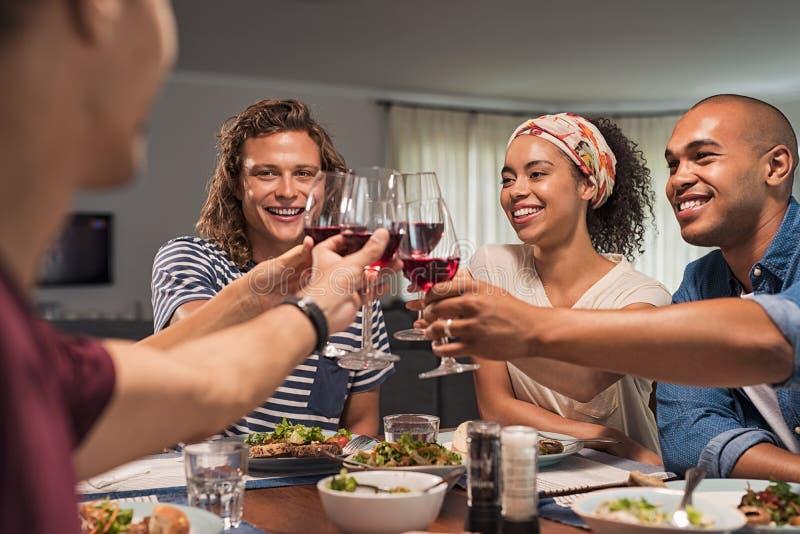 Vrienden die toost opheffen tijdens diner royalty-vrije stock foto's