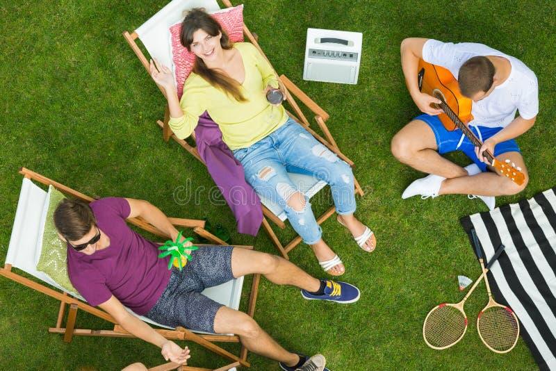 Vrienden die tuin van partij genieten stock afbeeldingen