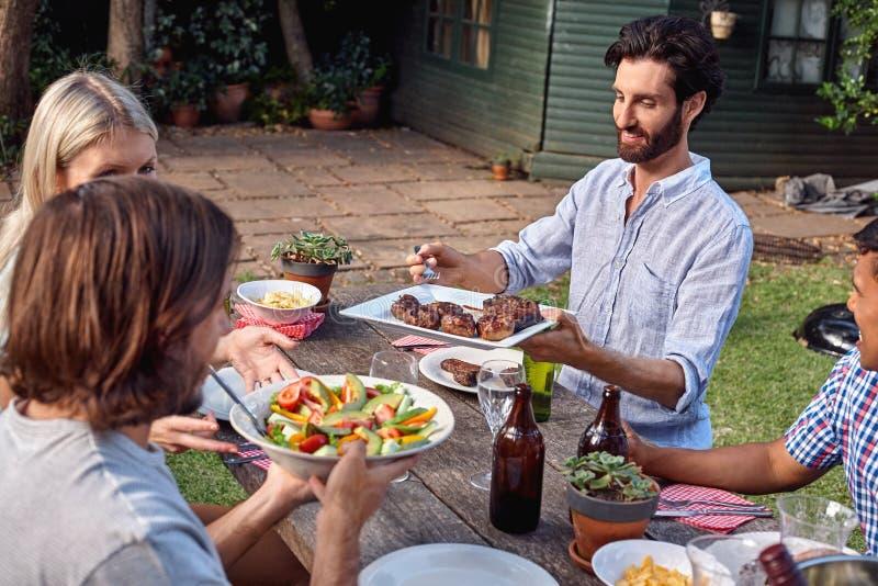 Vrienden die tuin van partij genieten stock fotografie