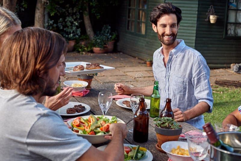 Vrienden die tuin van partij genieten stock afbeelding