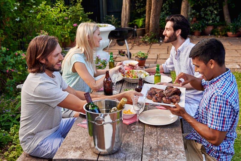 Vrienden die tuin van partij genieten royalty-vrije stock afbeeldingen