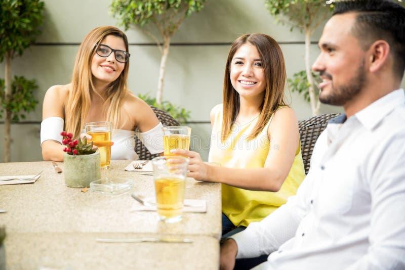 Vrienden die uit in een restaurant hangen royalty-vrije stock afbeeldingen