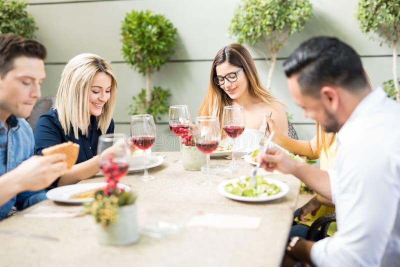 Vrienden die uit en een goede tijd eten hebben stock foto