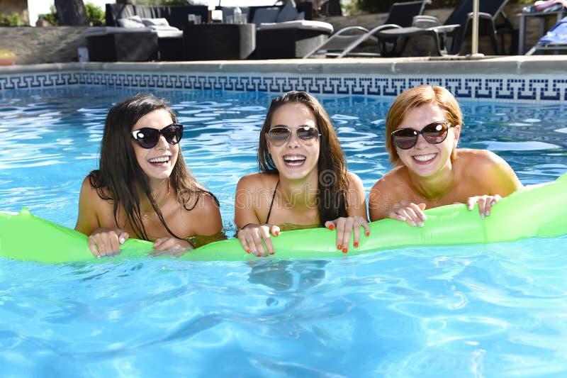 Vrienden die van het trio de gelukkige en mooie jonge meisje knuppel hebben royalty-vrije stock afbeelding