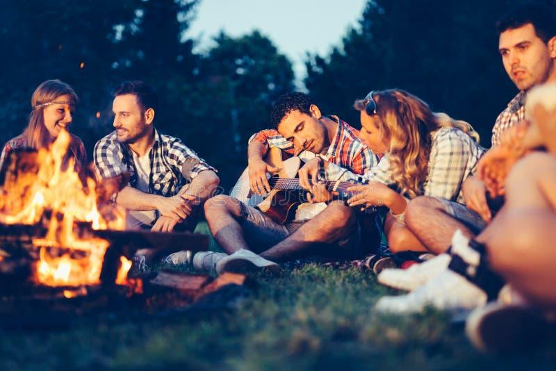 Vrienden die van muziek genieten dichtbij kampvuur bij nacht stock afbeeldingen