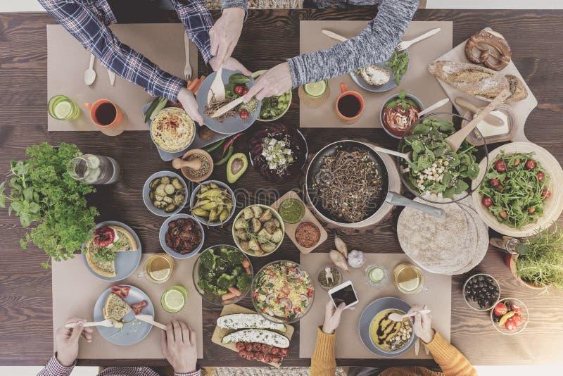 Vrienden die van nieuwe vegetarische recepten genieten royalty-vrije stock afbeeldingen