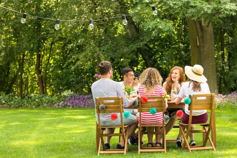 Vrienden die van vergadering genieten tijdens verjaardagspartij in de tuin royalty-vrije stock afbeeldingen