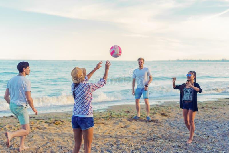 Vrienden die volleyball op een wild strand spelen tijdens zonsondergang royalty-vrije stock foto's