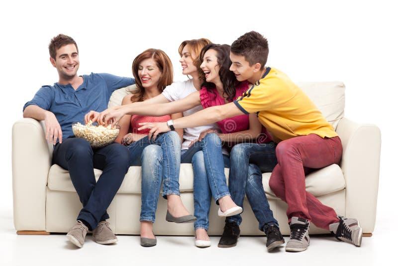 Vrienden die voor de popcorn bereiken stock afbeelding