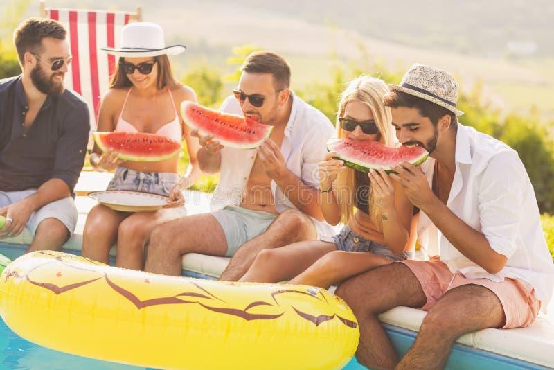 Vrienden die watermeloen eten stock foto