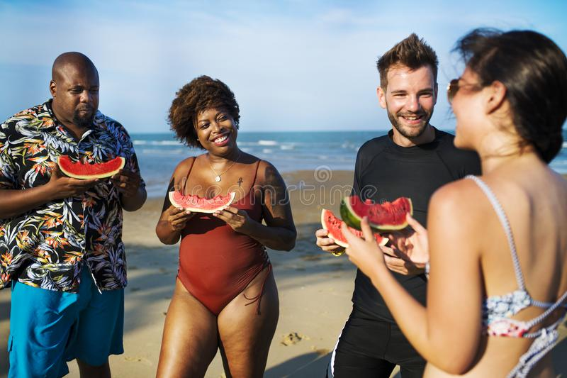 Vrienden die watermeloen op het strand eten royalty-vrije stock afbeelding