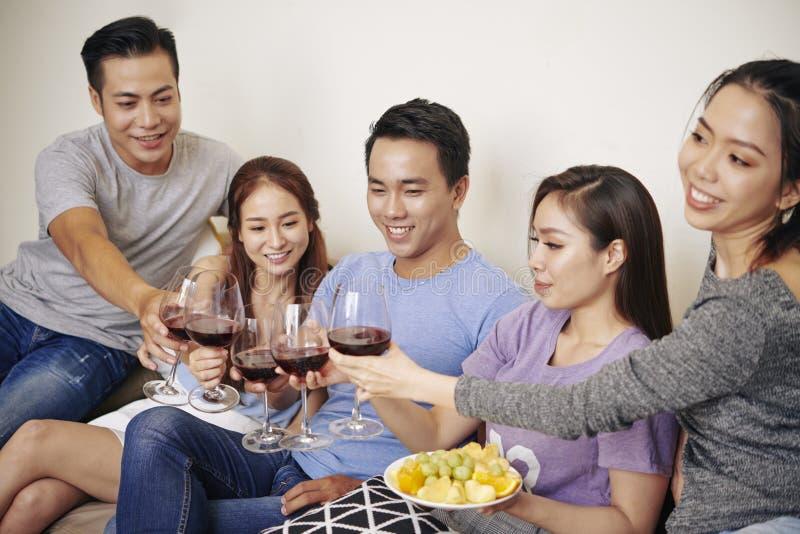 Vrienden die wijn drinken bij partij royalty-vrije stock foto