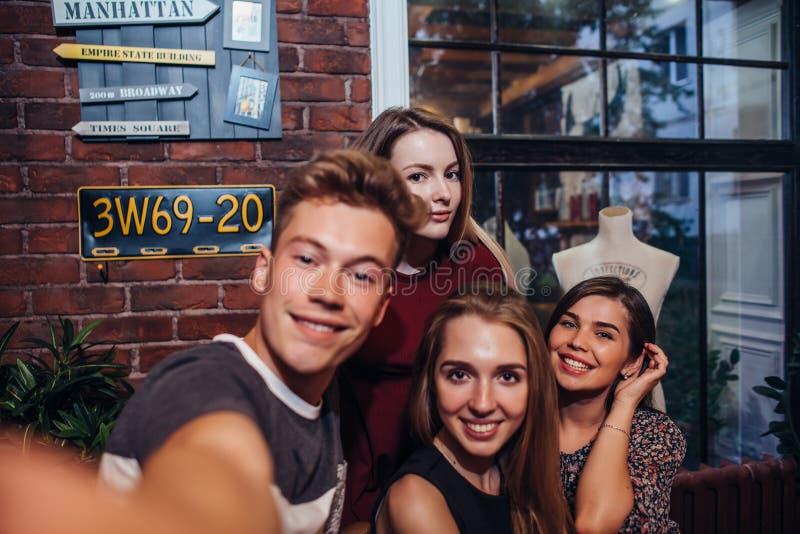 Vrienden die zelf-portretfoto, kerel nemen die een camera houden schietend selfie met zijn vrouwelijke vrienden die uit hangen stock fotografie