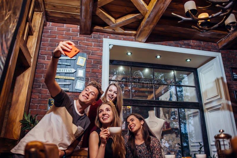 Vrienden die zelf-portretfoto, kerel nemen die een camera houden schietend selfie met zijn vrouwelijke vrienden die uit hangen stock foto's