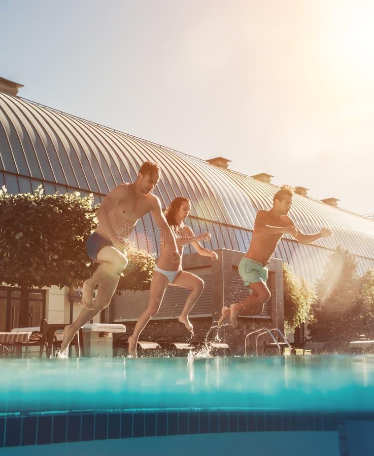 Vrienden die in zwembad springen stock afbeelding