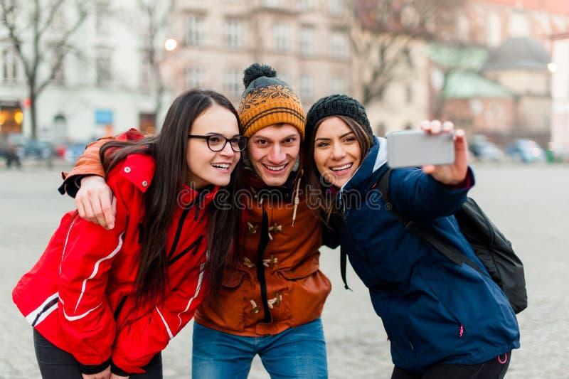 Vrienden in een toeristisch stadscentrum, die een selfie nemen stock afbeeldingen