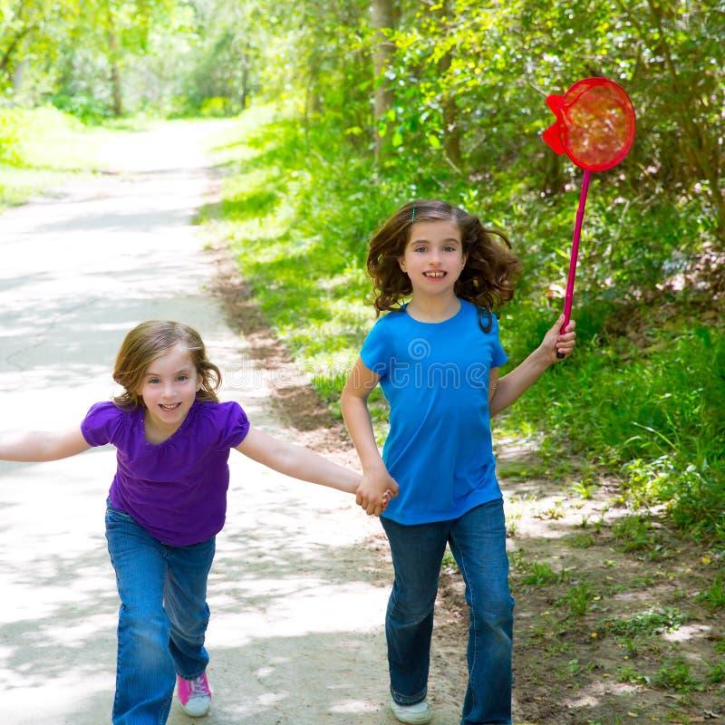Vrienden en zustermeisjes die in het bos gelukkige spoor lopen royalty-vrije stock foto