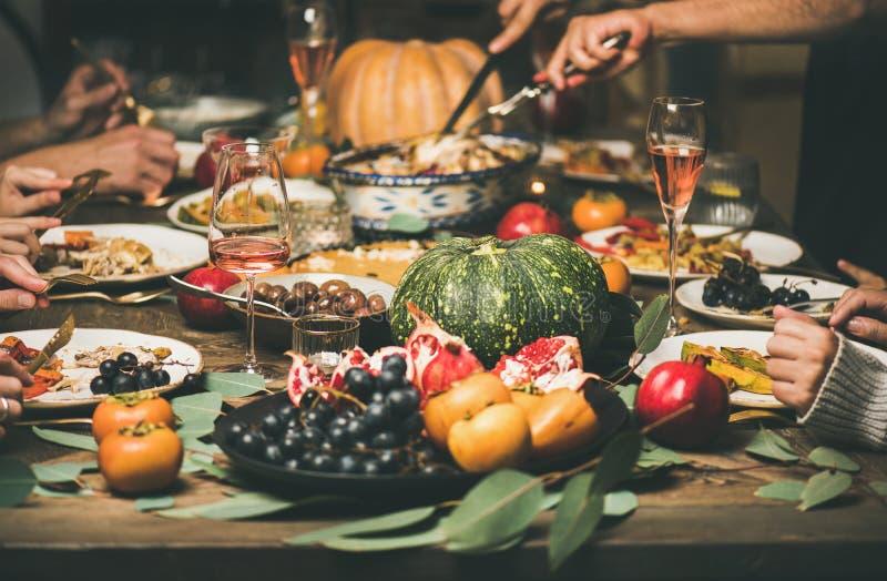 Vrienden of familie die verschillende snacks eten bij Feestelijke Kerstmislijst royalty-vrije stock afbeeldingen