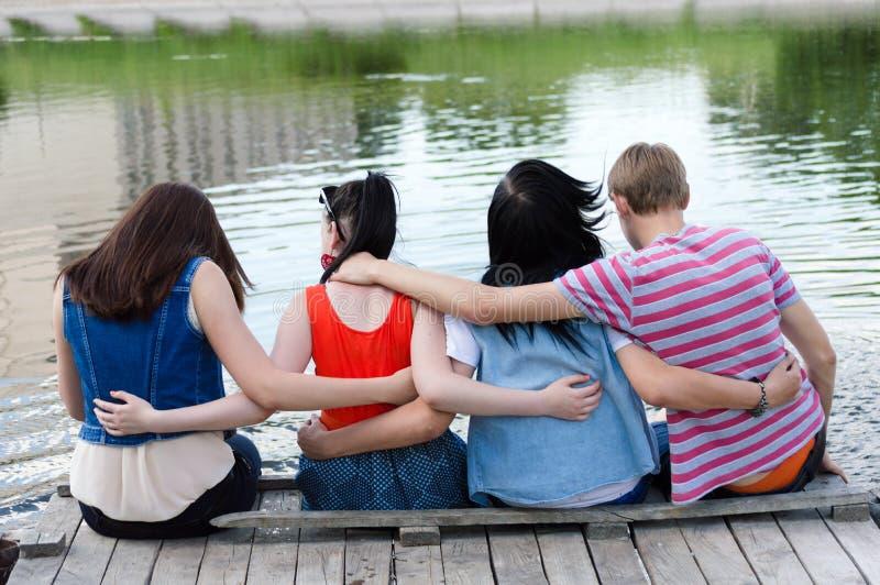Vrienden gelukkige zitting op brug bij de rivier stock afbeeldingen