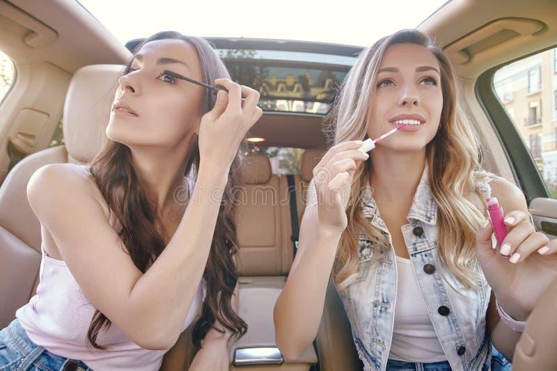 Vrienden het doen maakt omhoog in de auto stock fotografie