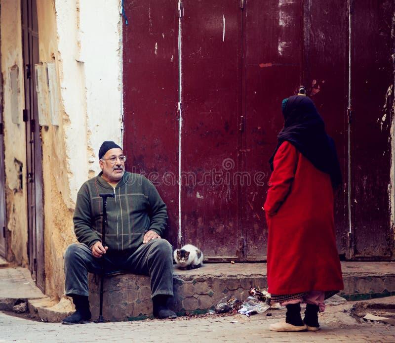 Vrienden hogere man, vrouwenbespreking in stadsstraat van Fes Medina met traditionele kleurrijke mousselinekleding en levensstijl stock foto's