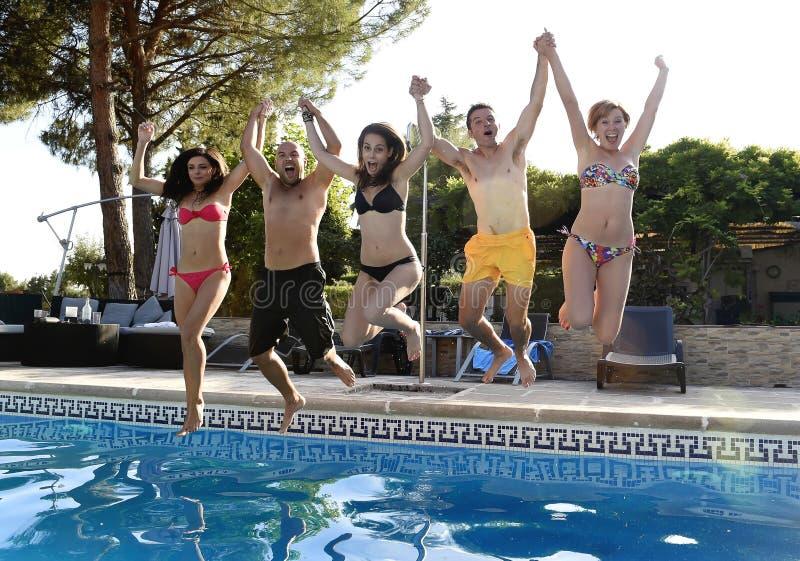 Vrienden jonge gelukkige aantrekkelijke mannen vrouwen die in bikini in de lucht aan hotel zwembad springen royalty-vrije stock afbeelding