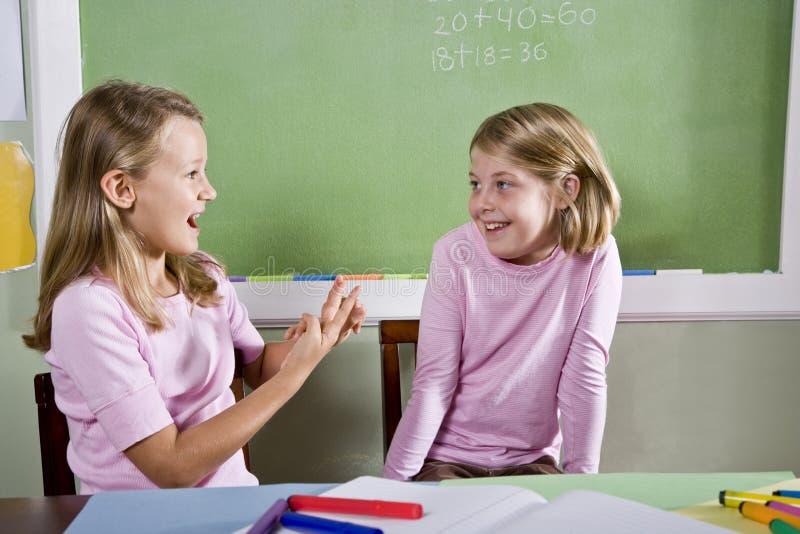 Vrienden in klasse het spreken stock foto's