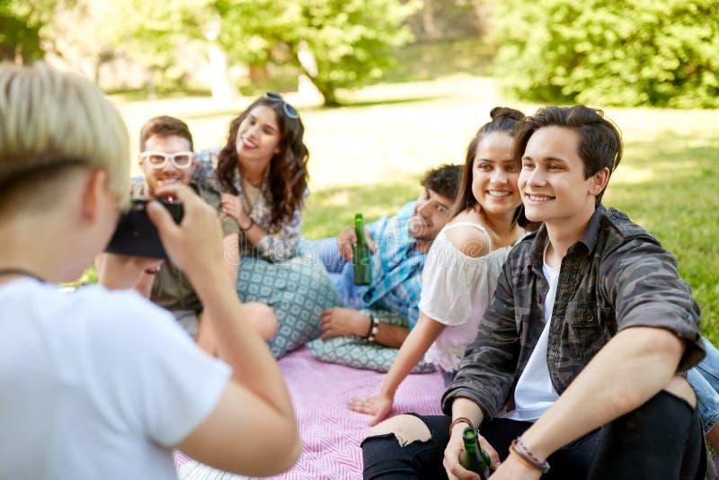 Vrienden met dranken die bij de zomerpicknick fotograferen royalty-vrije stock fotografie