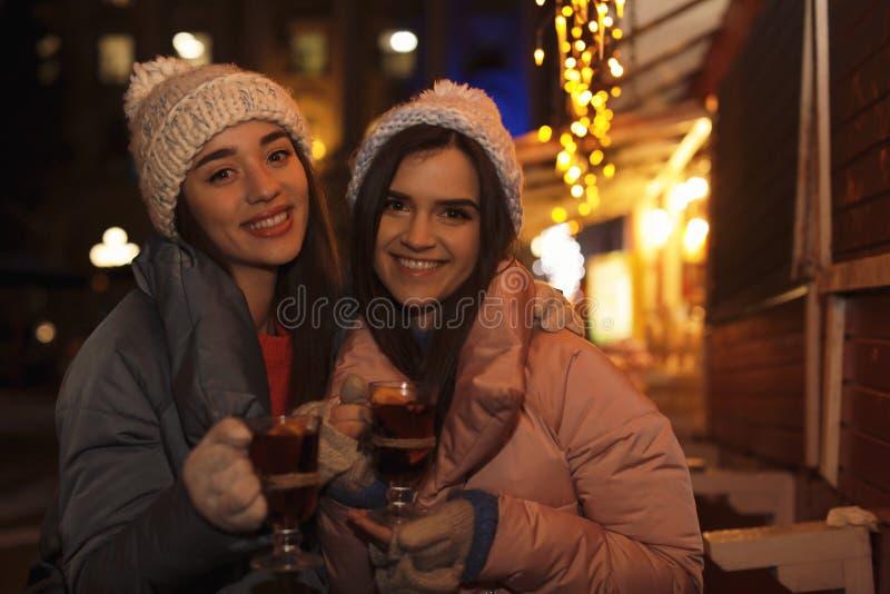 Vrienden met glaskoppen van overwogen wijn stock fotografie