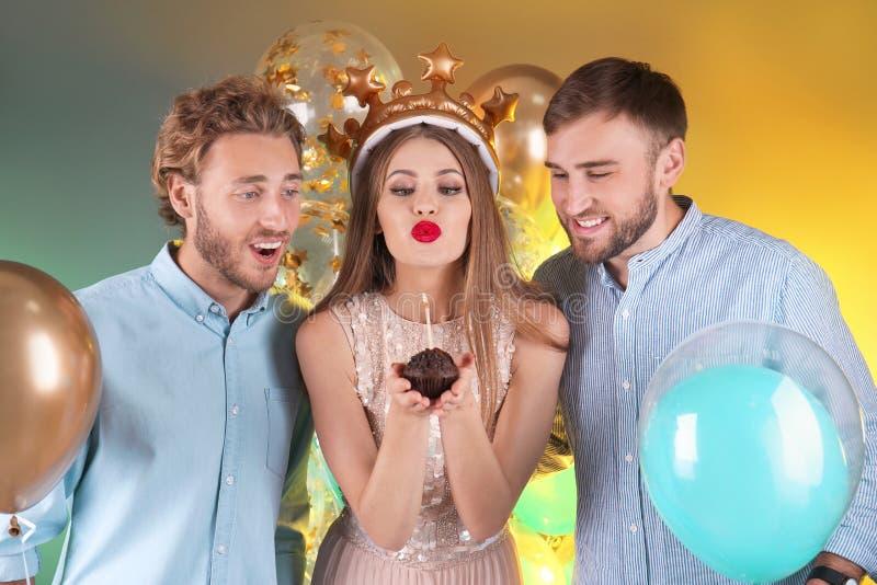 Vrienden met luchtballons en muffin op kleurenachtergrond stock afbeelding