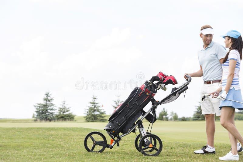 Vrienden met materiaal die terwijl het lopen bij golfcursus tegen duidelijke hemel spreken stock afbeeldingen