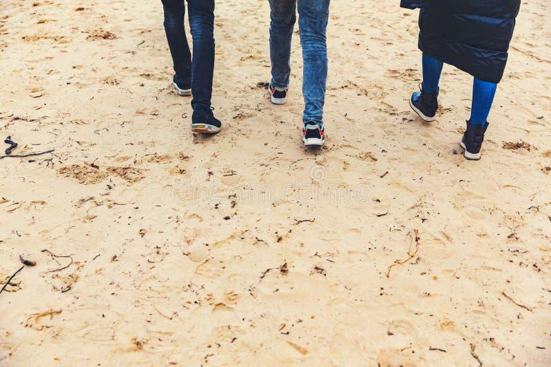 Vrienden op het strand Gang op het zand De herfst Koud weer Drie personen Reis royalty-vrije stock foto's