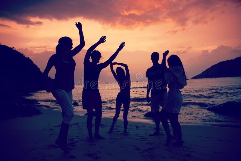 Vrienden op strand bij zonsondergang royalty-vrije stock afbeeldingen