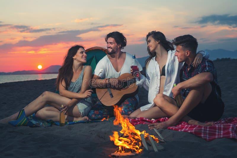 Vrienden rond de brand in zonsondergang op strand royalty-vrije stock fotografie