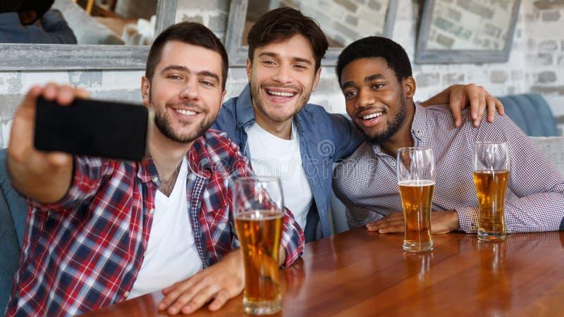 Vrienden selfie en glimlachen die, die bij bar rusten maken stock fotografie