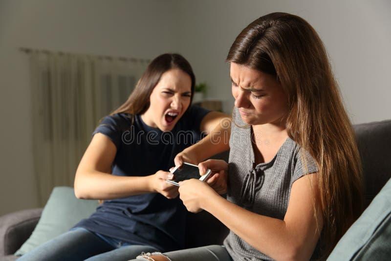 Vrienden of zusters die voor een slimme telefoon vechten stock afbeelding