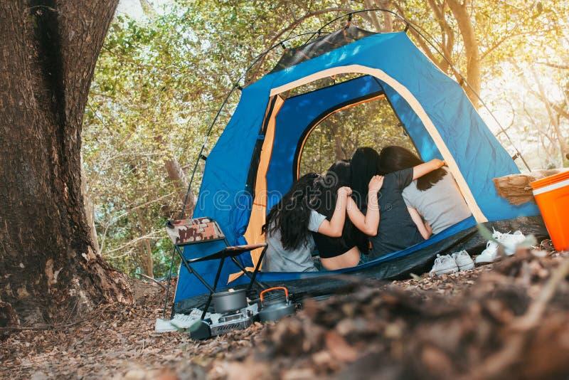 Vriendengroep Jonge Aziatische vrouwenomhelzing in tent het kamperen stock afbeeldingen