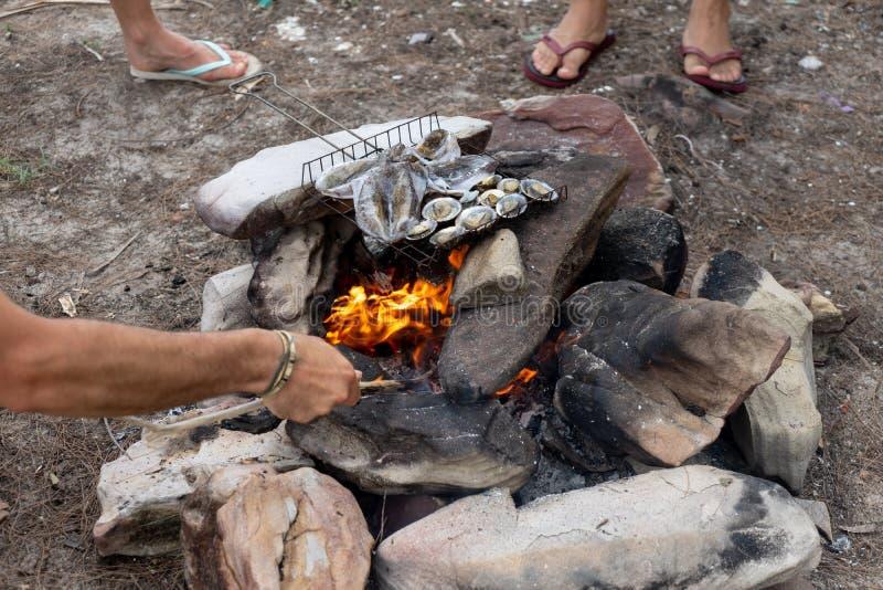 Vriendenpartij geroosterde pijlinktvis, shell zeevruchten met brand openlucht kooktijd in aard met vers voedsel in eilandstrand stock foto's