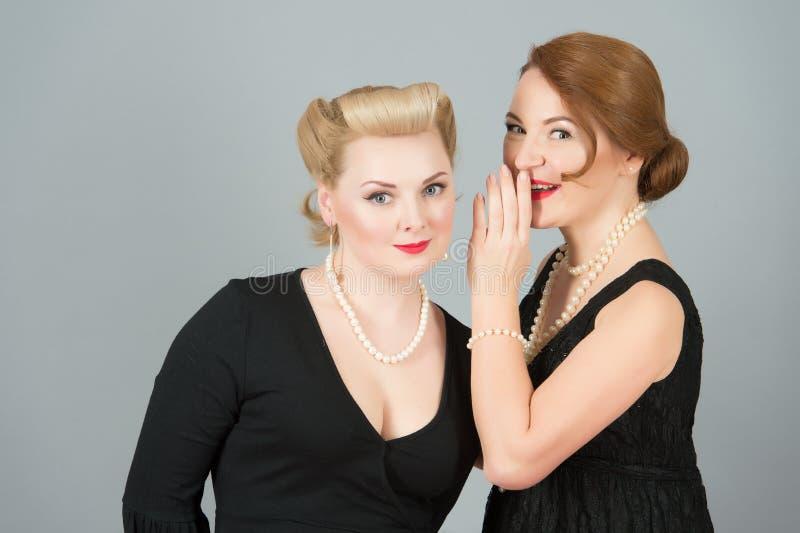 Vriendenvrouwen in het zwarte kleding roddelen Brunette en blonde speld-op gestileerde meisjes die van lippen aan oor met hand sp royalty-vrije stock afbeelding