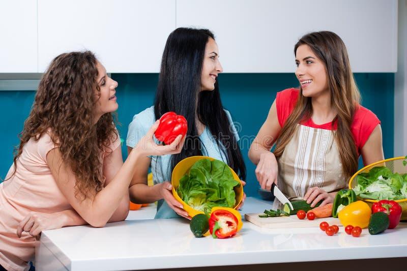 Vriendschap en gezonde levensstijl die thuis koken stock fotografie