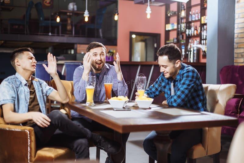 Vriendschap, sporten en vermaakconcept - gelukkige mannelijke vrienden die met bier op TV letten bij de bar stock foto